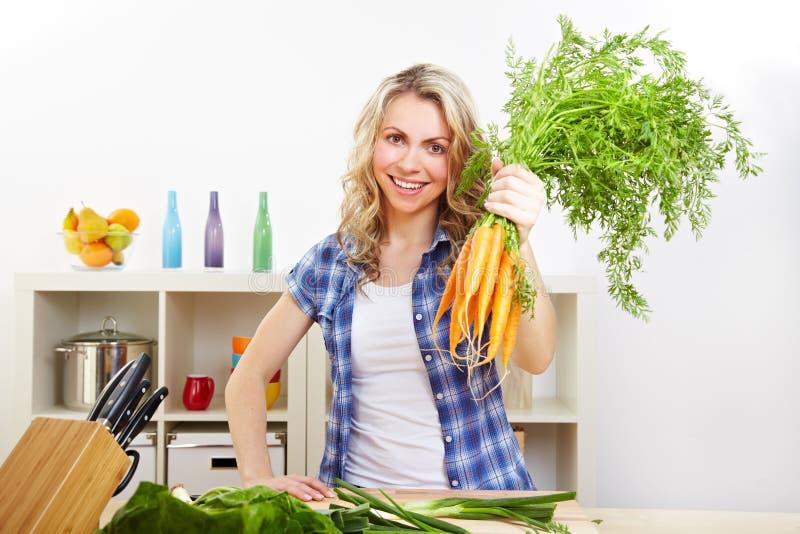 Mujer con el manojo de zanahorias imagenes de archivo