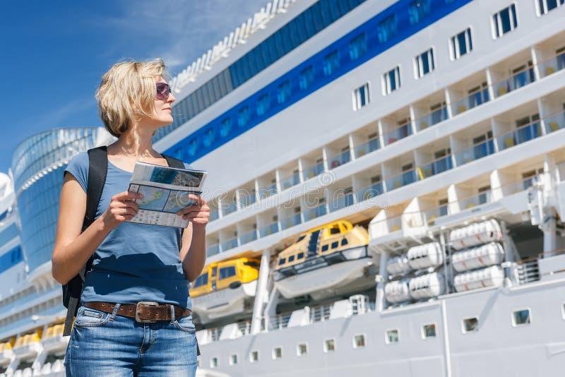 Mujer con el mapa, delante del trazador de líneas de la travesía foto de archivo