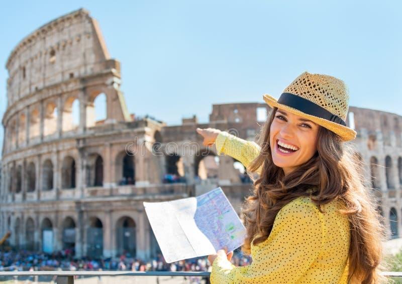 Mujer con el mapa que señala en colosseum en Roma foto de archivo