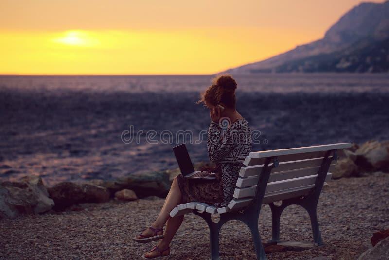 Mujer con el ordenador portátil en la playa de la tarde foto de archivo libre de regalías