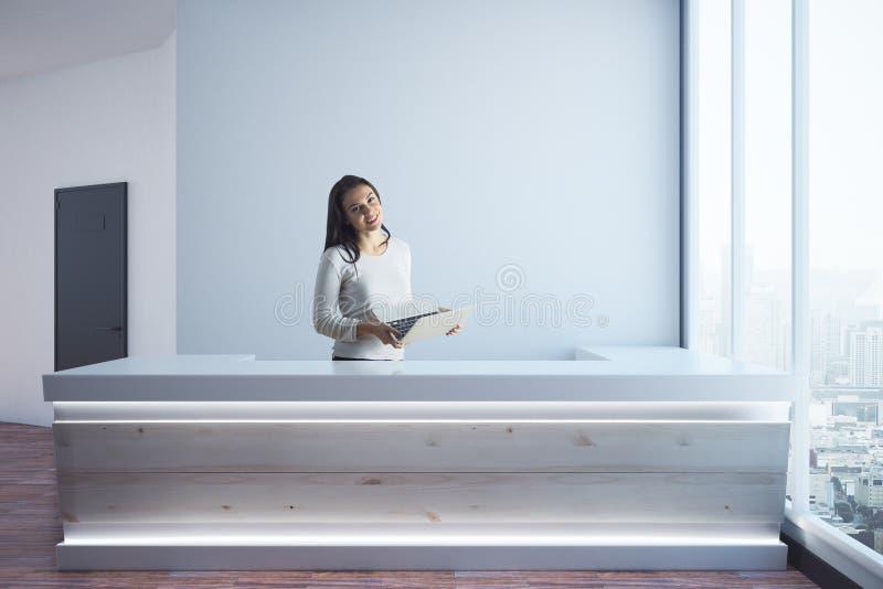 Mujer con el ordenador portátil en la recepción imagen de archivo