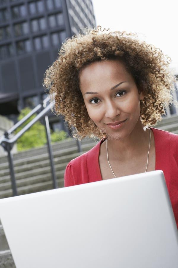 Mujer con el ordenador portátil en pasos al aire libre fotografía de archivo libre de regalías