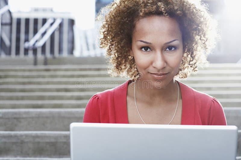 Mujer con el ordenador portátil en pasos al aire libre foto de archivo