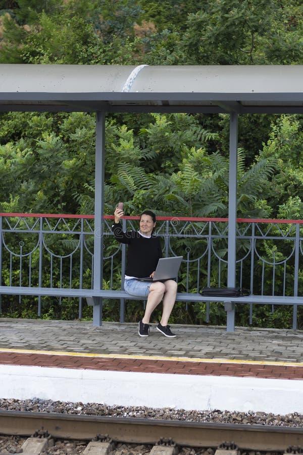 Mujer con el ordenador portátil y smartphone en el banco en el ferrocarril imagen de archivo