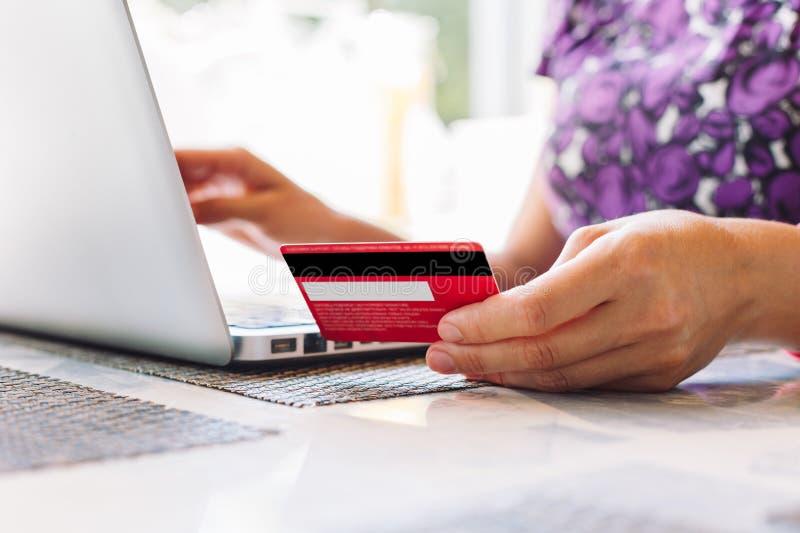 Mujer con el ordenador portátil y tarjeta de crédito en el café fotos de archivo libres de regalías