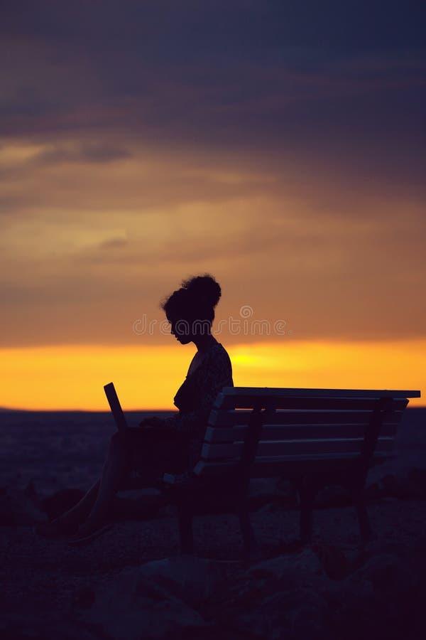 Mujer con el ordenador port?til en la playa de la tarde imagen de archivo libre de regalías