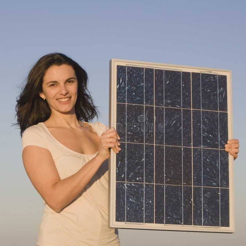 Mujer con el panel solar durante puesta del sol foto de archivo