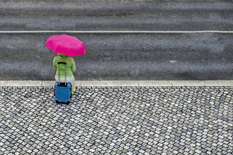 Mujer con el paraguas y la maleta que esperan cerca del camino imagenes de archivo