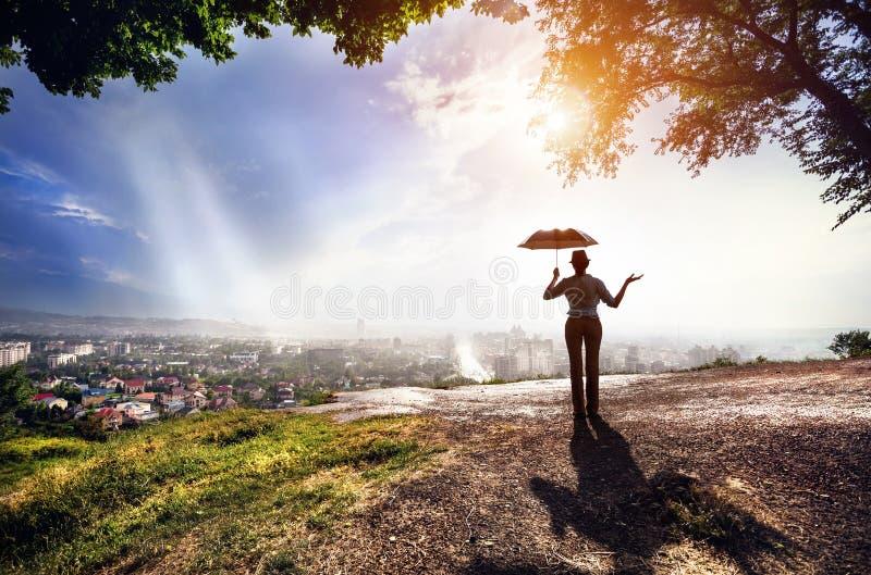 Mujer con el paraguas y paisaje urbano en la puesta del sol fotos de archivo