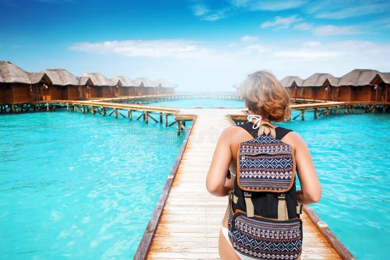 Mujer con el paseo de la mochila en el embarcadero en la isla tropical foto de archivo