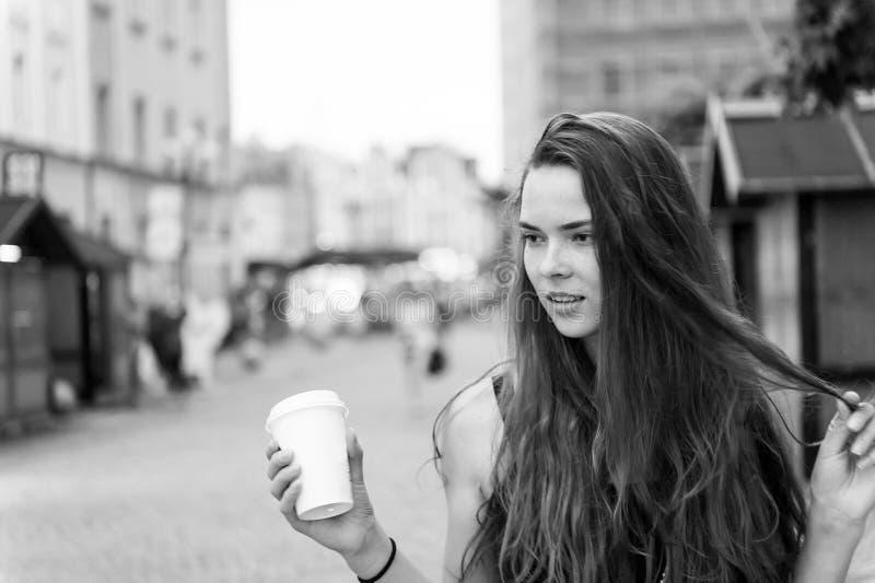 Mujer con el paseo para llevar de la bebida en la calle Taza de café disponible del control atractivo de la mujer Muchacha de la  foto de archivo libre de regalías