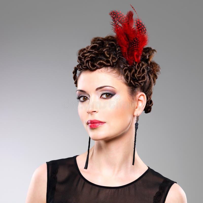 Mujer con el peinado de la moda con la pluma roja en pelos fotos de archivo libres de regalías