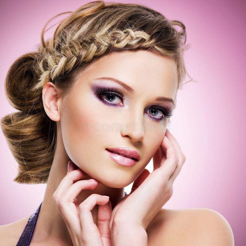 Mujer con el peinado de la moda y el maquillaje rosado fotos de archivo