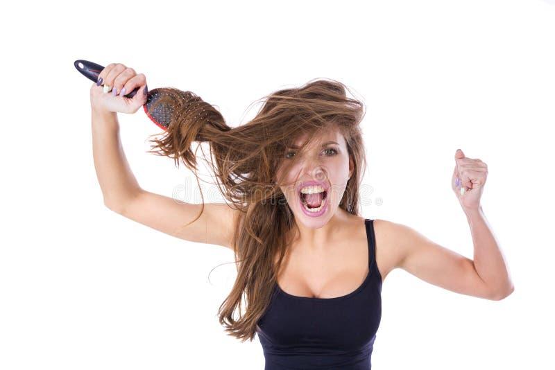 Mujer con el peine en pelo enredado gritos Aislado en el concepto blanco de la salud del pelo del fondo imagen de archivo