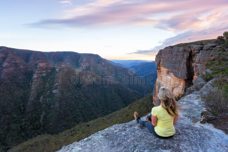 Mujer con el pelo barrido por el viento sentada al borde de los acantilados imagenes de archivo