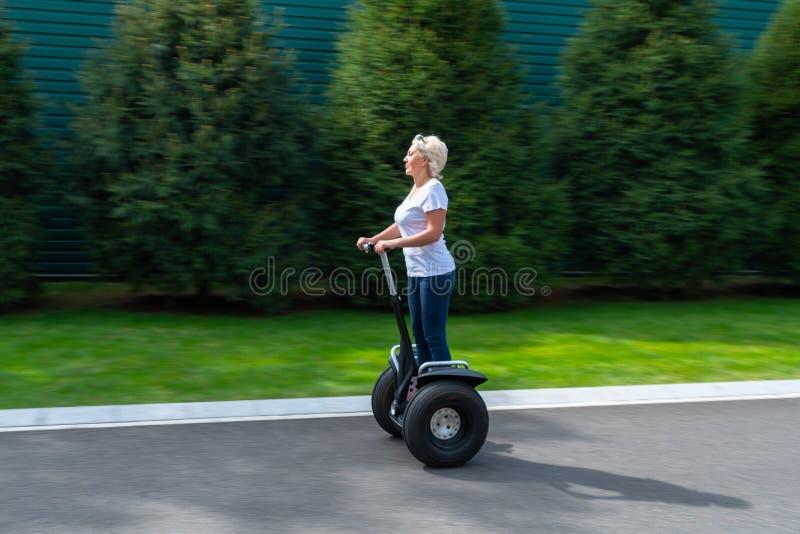 Mujer con el pelo blanco que monta el transportador personal imagen de archivo