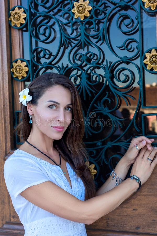 Mujer con el pelo largo con la flor del plumeria del frangipani en el fondo de una puerta de madera imagen de archivo libre de regalías