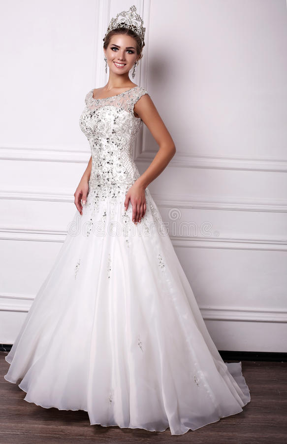 Mujer con el pelo oscuro en vestido de boda lujoso y corona preciosa fotografía de archivo