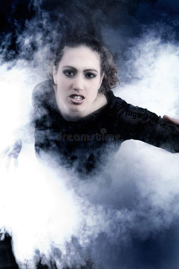 Mujer con el pelo rizado largo que se arrastra de humo foto de archivo libre de regalías