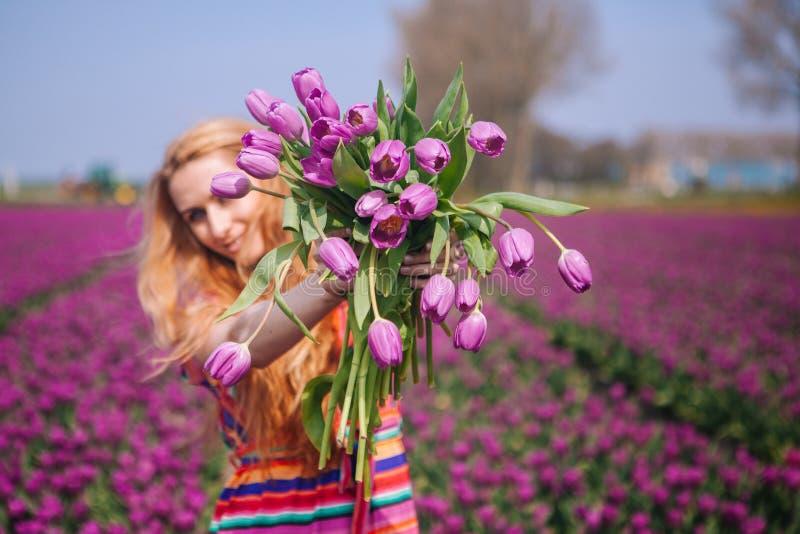 Mujer con el pelo rojo largo que lleva un vestido rayado que sostiene un ramo de flores p?rpuras de los tulipanes en fondo en cam foto de archivo