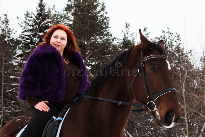 Mujer con el pelo rojo y el caballo grande al aire libre en invierno foto de archivo