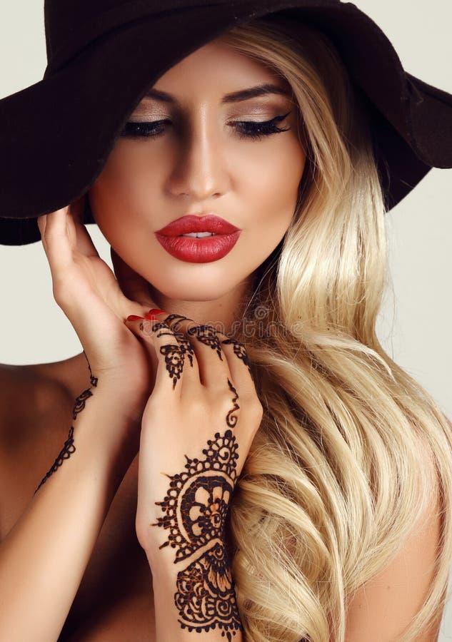 Mujer con el pelo rubio con maquillaje de la tarde y tatuaje de la alheña en las manos imagen de archivo libre de regalías