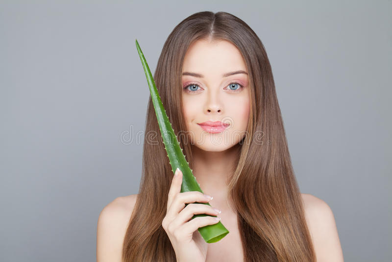Mujer con el pelo sano largo que sostiene la hoja verde del áloe fotos de archivo libres de regalías