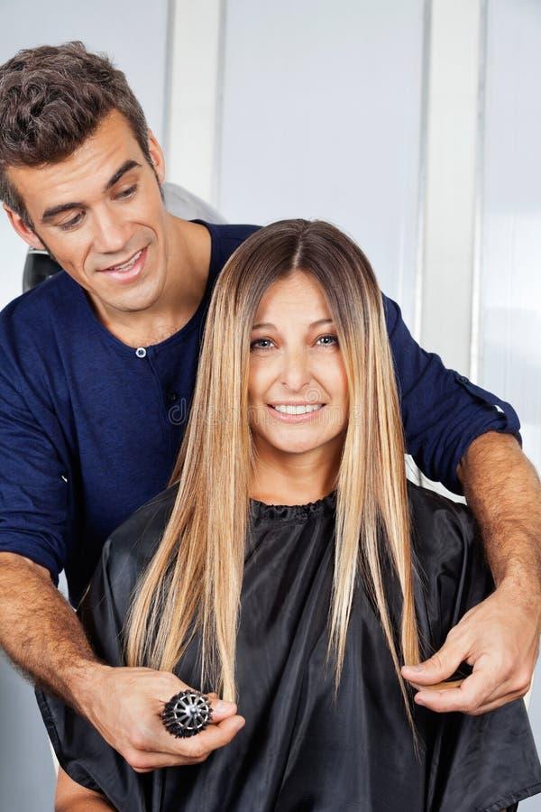 Mujer con el peluquero Measuring Her Hair en el salón imagenes de archivo