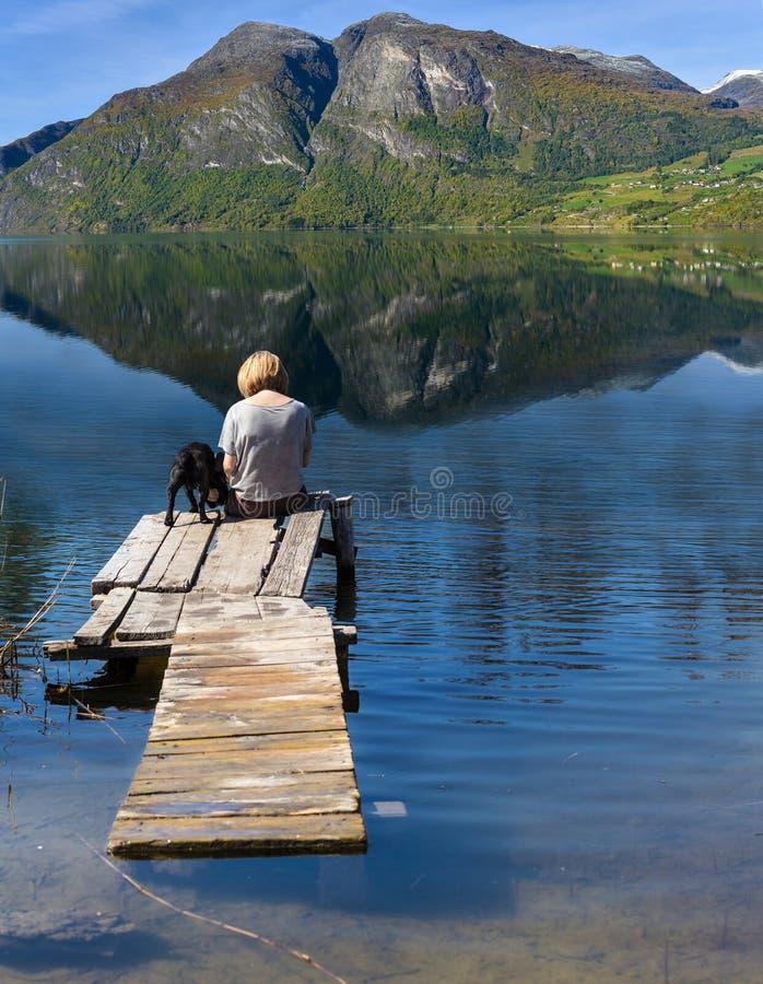 Mujer con el perro que se sienta en el puente fotos de archivo libres de regalías