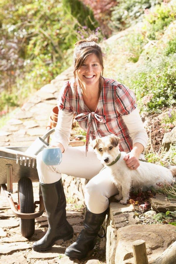 Mujer con el perro que tiene descanso para tomar café foto de archivo libre de regalías