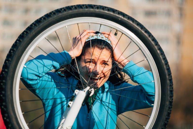 Mujer con el problema de la bici de la fijación del dolor de cabeza imagen de archivo libre de regalías