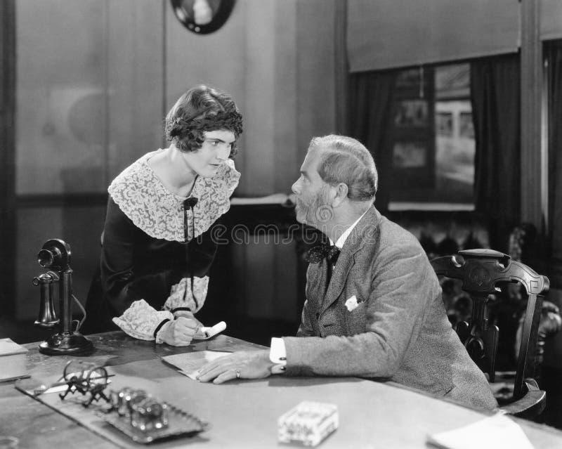 Mujer con el puño apretado en una oficina que se deslumbra en su jefe (todas las personas representadas no son vivas más largo y  imágenes de archivo libres de regalías