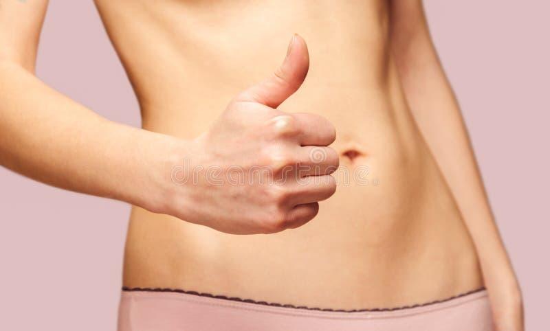 Mujer con el pulgar del gesto para arriba delante de su vientre imagen de archivo