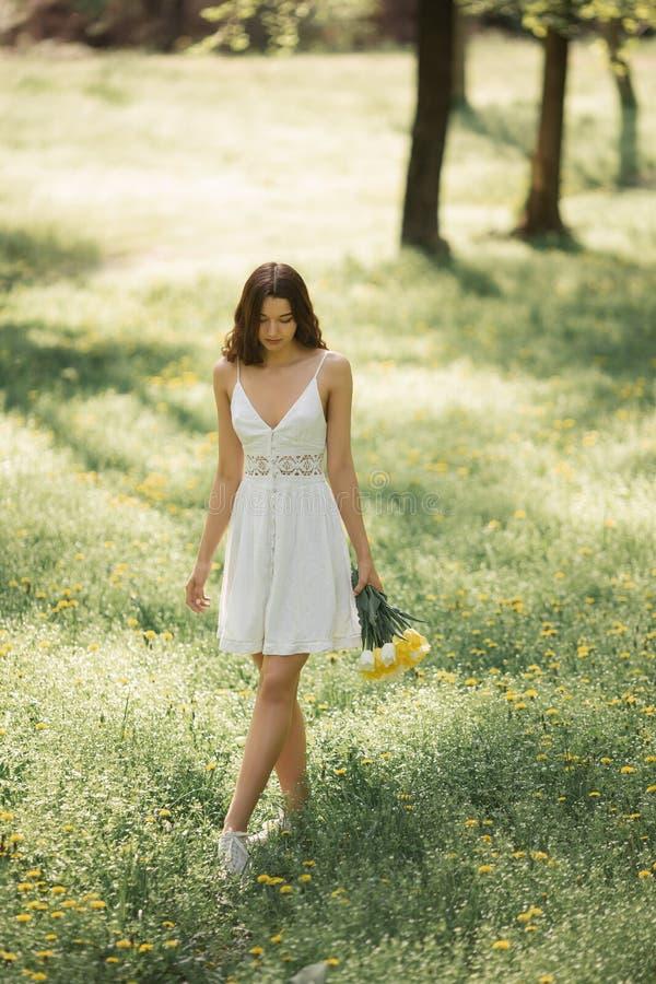 Mujer con el ramo de las flores de la primavera al aire libre imágenes de archivo libres de regalías
