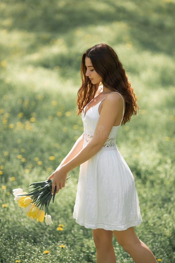 Mujer con el ramo de las flores de la primavera al aire libre fotografía de archivo libre de regalías