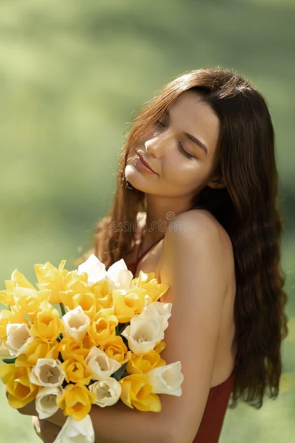 Mujer con el ramo de las flores de la primavera al aire libre fotos de archivo libres de regalías