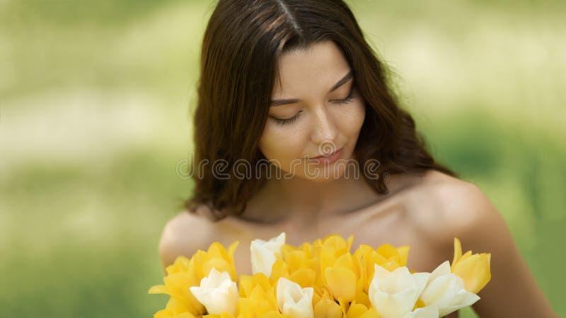Mujer con el ramo de las flores de la primavera al aire libre imagenes de archivo