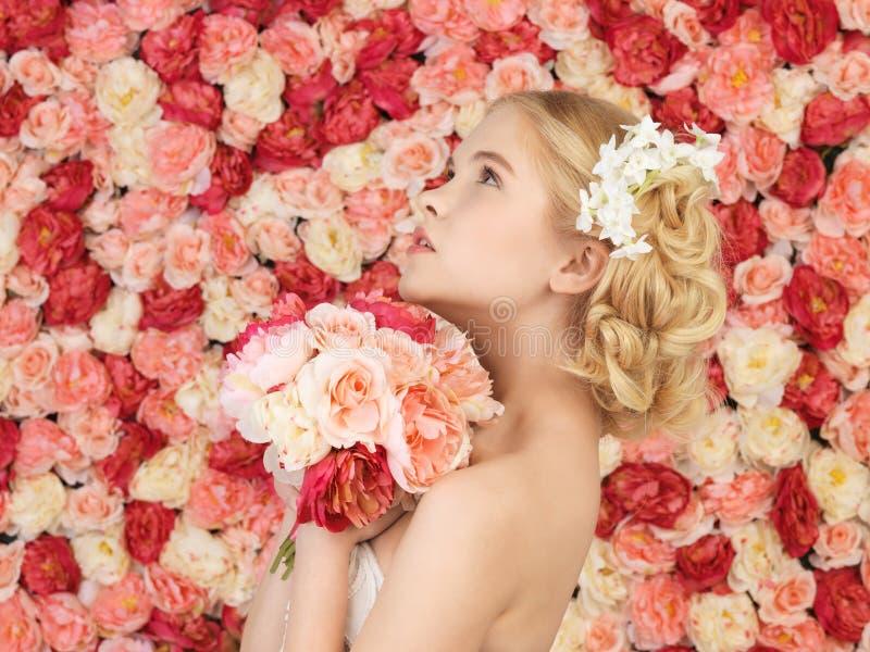 Mujer con el ramo y fondo por completo de rosas imagen de archivo libre de regalías