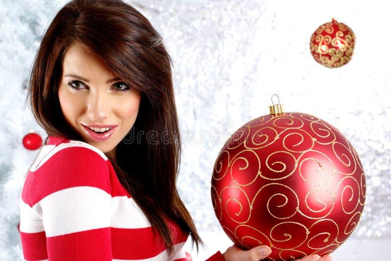 Mujer con el regalo al lado del árbol de navidad blanco imagen de archivo