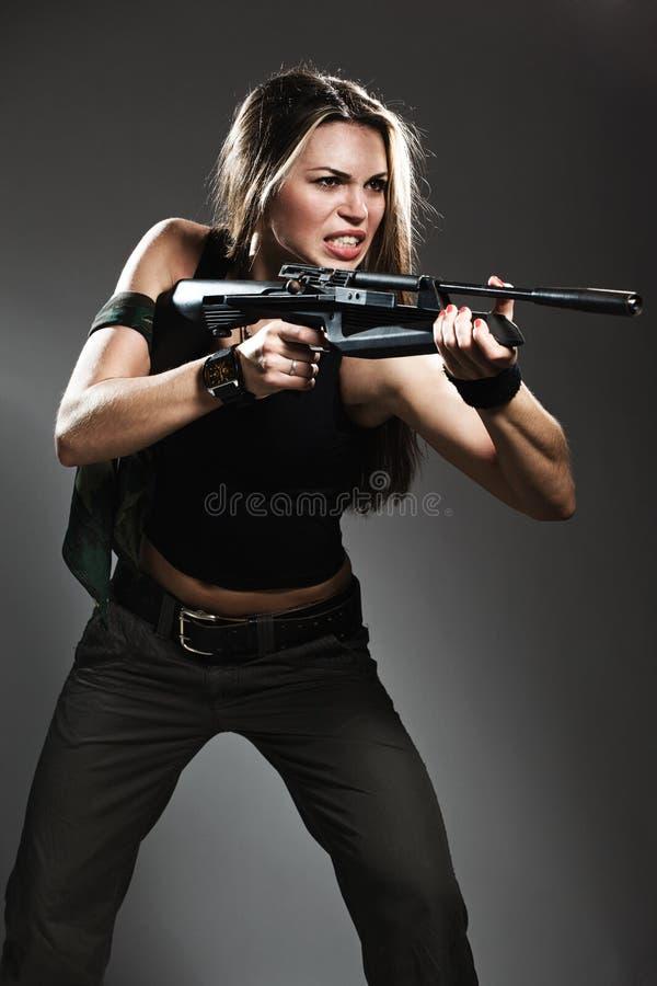 Mujer con el rifle en obscuridad fotos de archivo