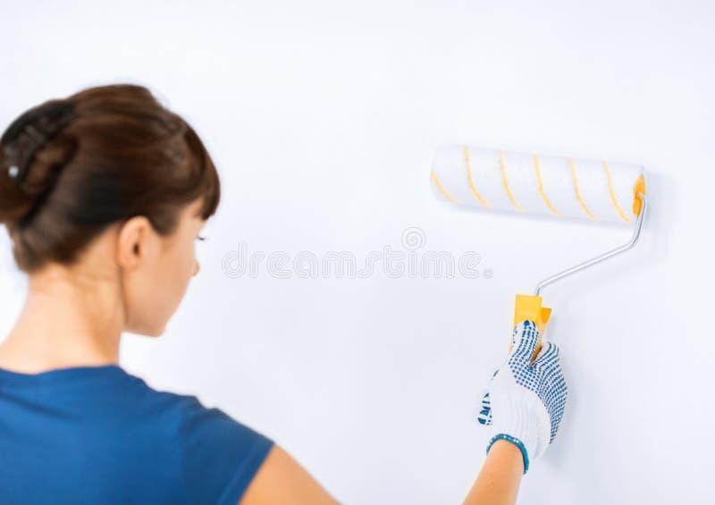 Mujer con el rodillo y la pintura que colorean la pared foto de archivo