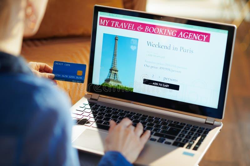 Mujer con el sitio en línea del viaje en el ordenador portátil que sostiene la tarjeta de crédito azul imagen de archivo