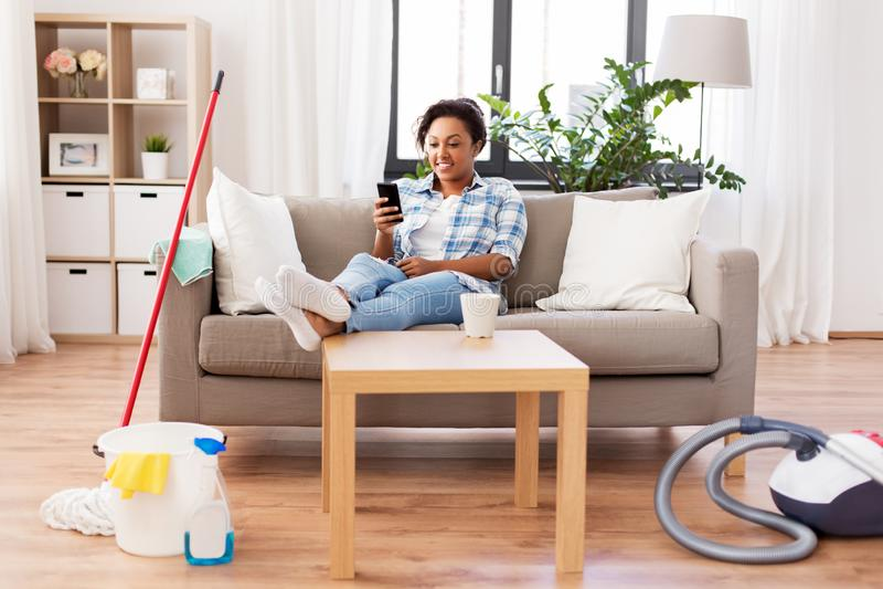 Mujer con el smartphone que descansa despu?s de la limpieza casera imagenes de archivo