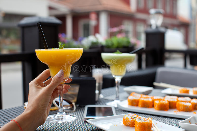 Mujer con el smoothie fresco de la papaya en barra de sushi el día de verano fotos de archivo