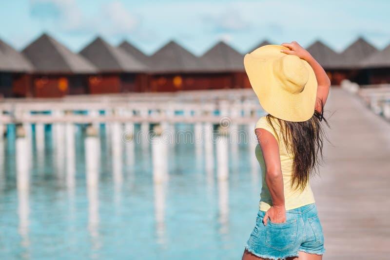 Mujer con el sombrero amarillo que se relaja en la piscina en centro turístico exótico fotos de archivo libres de regalías