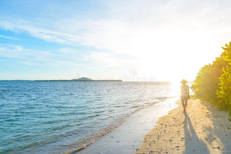 Mujer con el sombrero asi?tico tradicional que se relaja en la playa tropical en contraluz en la gente real de la puesta del sol  foto de archivo