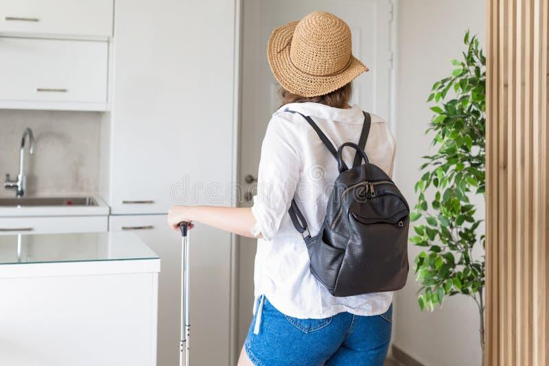 Mujer con el sombrero de la maleta y de paja en camisa y pantalones cortos que van a la puerta y que esperan un taxi Aliste para  imagenes de archivo