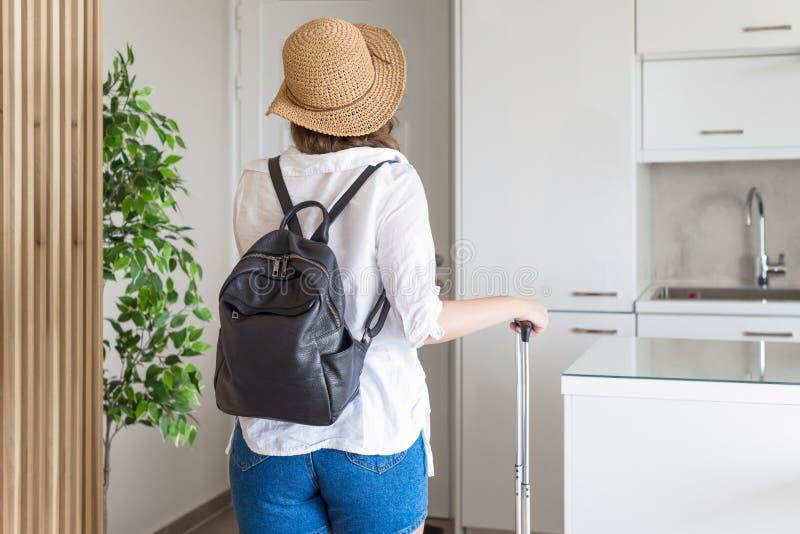 Mujer con el sombrero de la maleta y de paja en camisa y pantalones cortos que van a la puerta y que esperan un taxi Aliste para  fotos de archivo libres de regalías