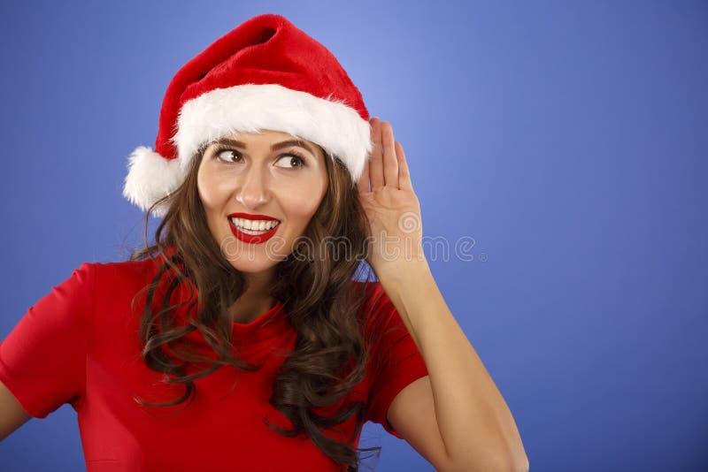 mujer con el sombrero de la Navidad con la mano al oído fotos de archivo