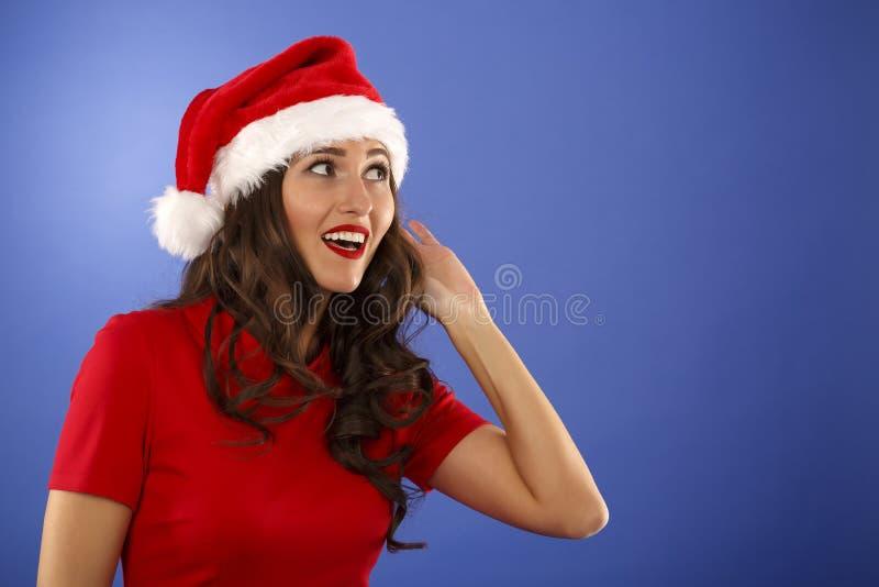 mujer con el sombrero de la Navidad con la mano al oído foto de archivo